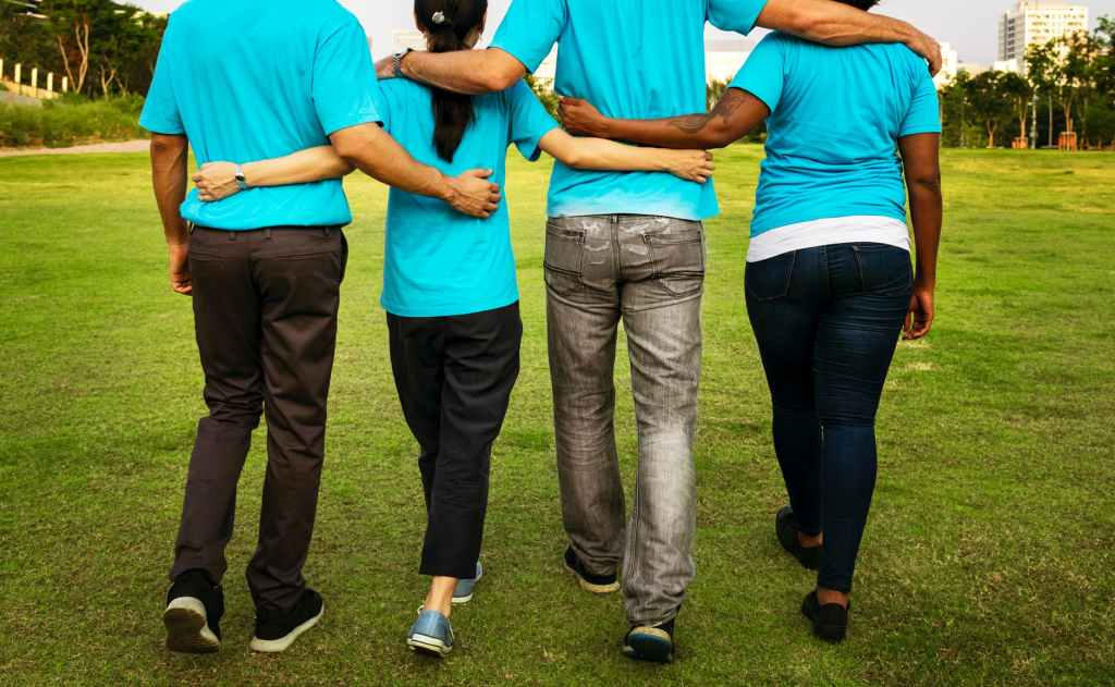 four people walking while holding each others arms